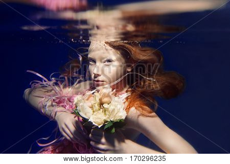 portrait of young beautiful red hair girl in pink dress and with roses underwater