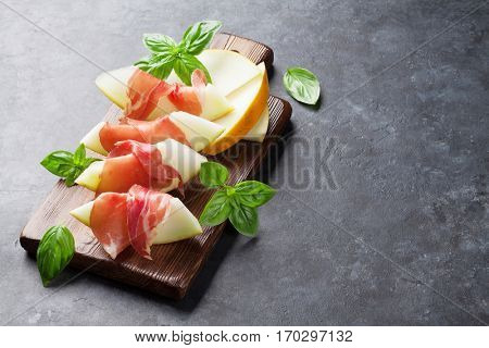 Fresh melon with prosciutto and basil. Antipasti. On dark stone table with copy space