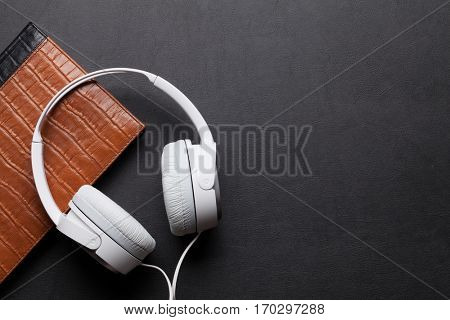 Headphones and notepad on black leather desk table. Music concept. Top view with copy space