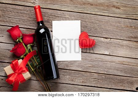 Valentines day greeting card. Red wine, roses and gift box on wooden table. Top view with copy space