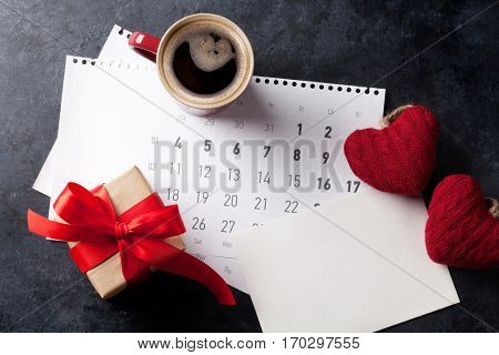 Valentines day greeting card. Coffee cup and gift box over february calendar on stone table. Top view with space for your greetings
