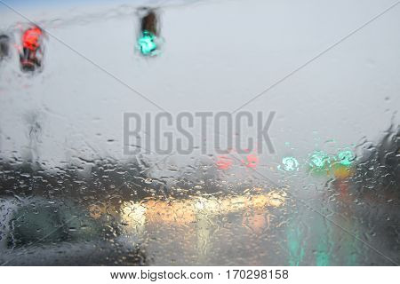 Rain drops on the car front window with the blurred traffic lights