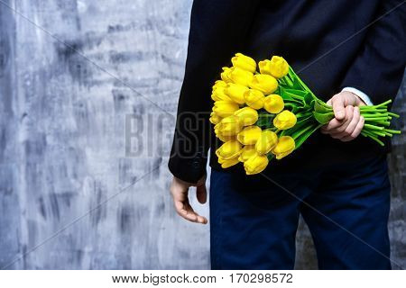 A man in elegant black suit hides a bouquet of tulips behind his back. Valentine's Day, Women's Day, Mother's Day. Wedding concept.