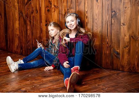 Modern generation. Two laughing girls, older and younger sister sitting together on a floor with their smartphones.