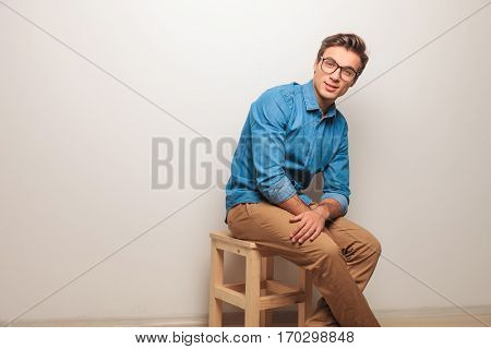side view of a seated casual man sitting on a chair in studio and smiles to the camera