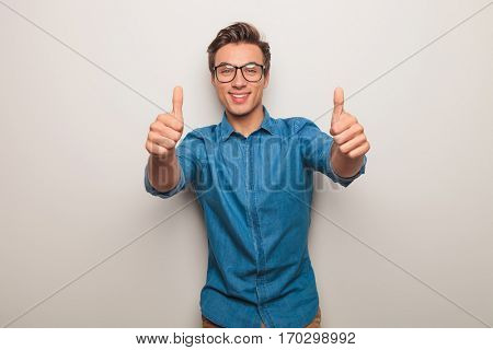 happy young casual man making the ok thumbs up hand sign on grey studio background