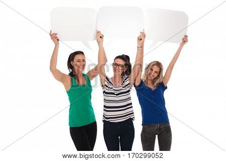 three happy women holding blank speech bubbles over their heads on white studio background