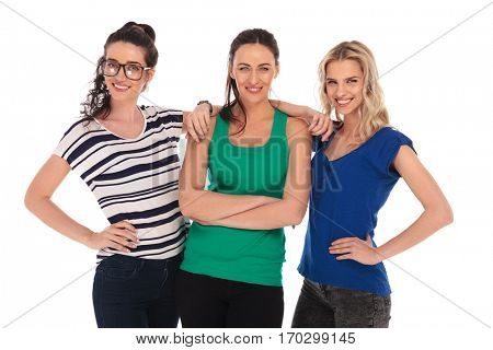 three relaxed young women posing together in studio on white background