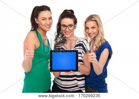 three smiling young women showing the blank screen on a tablet pad computer and make the ok thumbs up hand sign , on white background