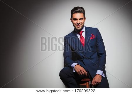happy young businessman in elegant suit resting on a chair in studio