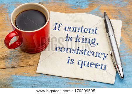 If content is king, consistency is queen - blogging and social media tip - handwriting on a napkin with a cup of coffee