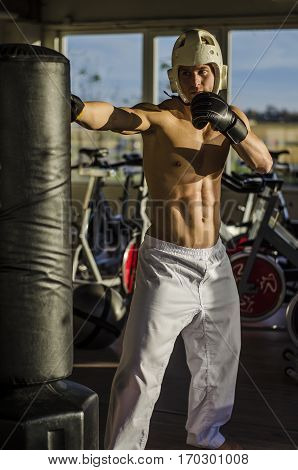 Shirtless handsome muscular young man in gym giving punch to punching bag, wearing boxing gloves and helmet
