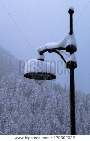 Traditional wrought iron lamppost covered in snow from storm turning forest and valley snowy white