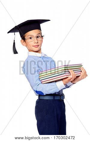 Smart school boy in academic hat and glasses sitting with books. Educational concept. Isolated over white background.