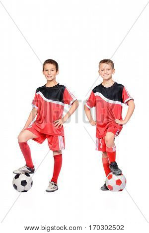Sports and activities for children. Two boys football players posing in sportswear with soccer ball. Isolated over white background. Copy space.
