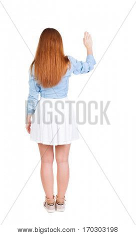 back view of woman. Young woman in dress presses down on something. Isolated over white background. Rear view people collection. backside view of person. she holds his hand open, palm forward