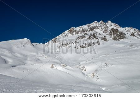 Winter mountain landscape freshly snow covered with few fresh ski tracks leading down from mountain ridge