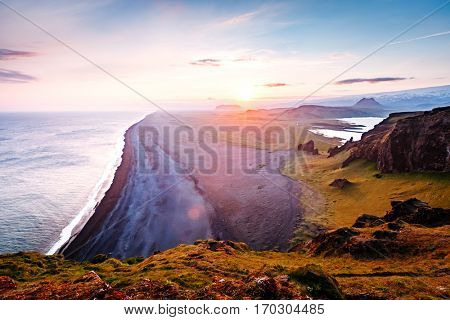 Amazing black sand of lava in the beach on small peninsula. Popular tourist attraction. Unusual and gorgeous scene. Location place Sudurland, cape Dyrholaey, coast of Iceland, Europe. Beauty world.