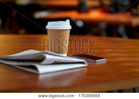 technology, break, mass media and news concept - coffee drink in paper cup, smartphone and newspaper on cafe table