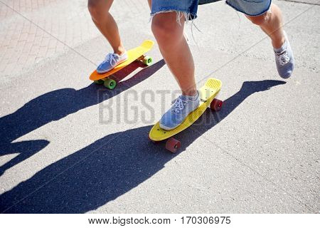 summer, extreme sport and people concept - teenage couple riding short modern cruiser skateboards on city road