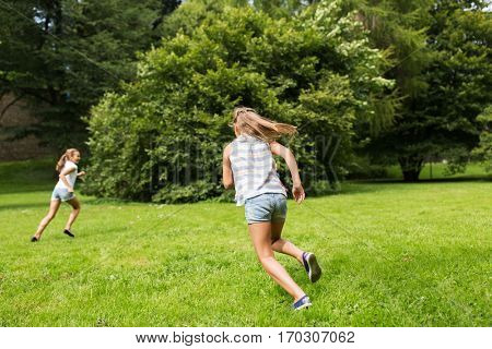 friendship, childhood, leisure and people concept - happy kids or friends playing catch-up game and running in summer park