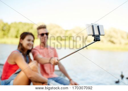 technology, vacation and people concept - happy teenage couple taking picture by smartphone selfie stick and sitting on river berth at summer