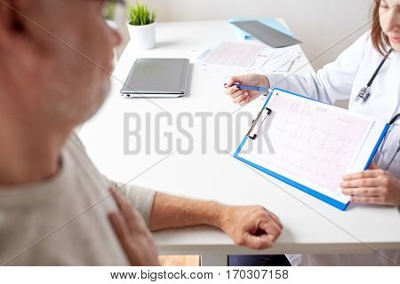 medicine, old age, healthcare, cardiology and people concept - senior man and doctor showing cardiogram on clipboard in medical office at hospital