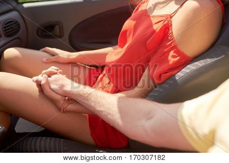 love, road trip, travel and people concept - happy couple driving in cabriolet car and holding hands