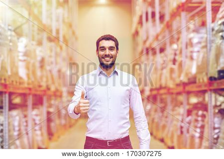wholesale, logistic, business, export and people concept - happy man at warehouse showing thumbs up gesture