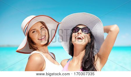 summer holidays, travel, people and vacation concept - happy young women in hats over over exotic tropical beach background