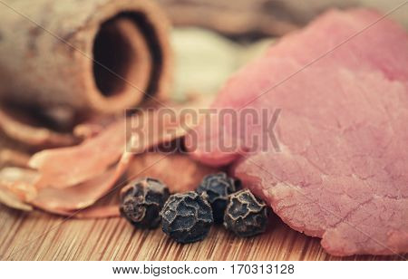 Raw beef with spices on wooden surface
