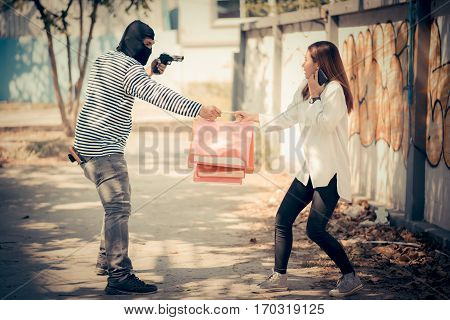 Street thief stealing young woman shopping bag and threatening with gun Vintage tone style