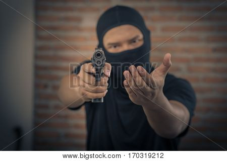 Thief pointing a gun Terrorism and theft concept