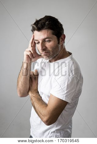 young attractive man gesturing thoughtful as if daydreaming for a future plan or project thinking isolated on grey background looking worried and sad