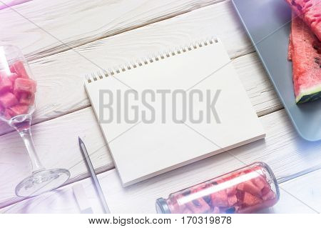 Blank sketch book on the table with slices of watermelon