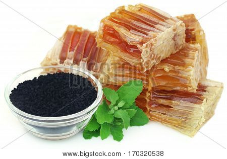 Honey with black cumin and tulsi leaves over white background