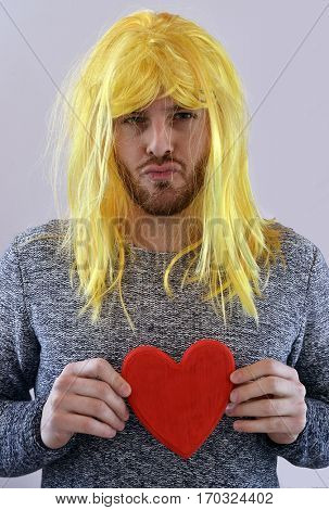 lover day funny man portrait holding heart wearing blonde wig.