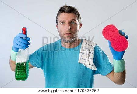 portrait of domestic service man or tired husband angry and stressed doing house cleaning with spray bottle and sponge in annoyed and busy face expression isolated even background