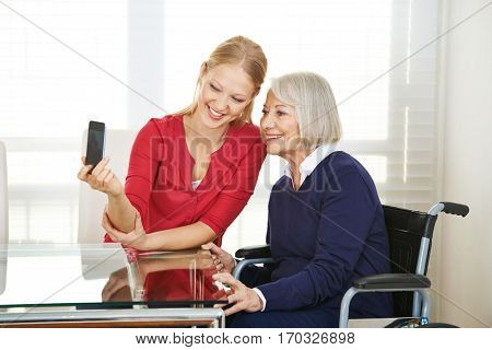 Family taking selfie of granddaughter and grandmother with a smartphone