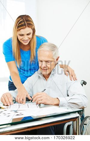 Daughter helping senior father in wheelchair at home solving sudoku puzzles