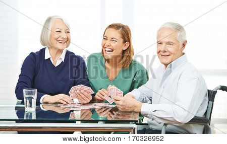 Happy nurse playing cards with senior couple in nursing home