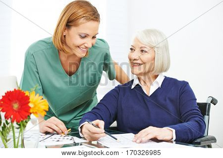 Old woman in wheelchair doing memory training in a nursing home
