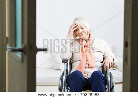 Old lonely woman in wheelchair at home looking sad