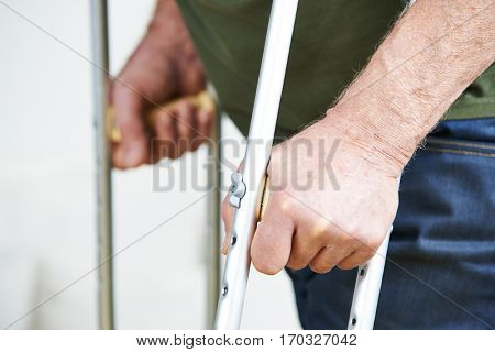 Hands of senior man holding on to crutches