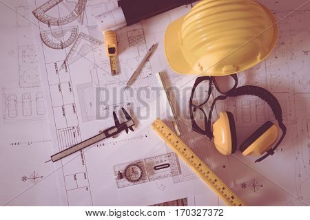Construction plans with helmet and drawing tools on blueprints  ( Filtered image processed vintage effect. )