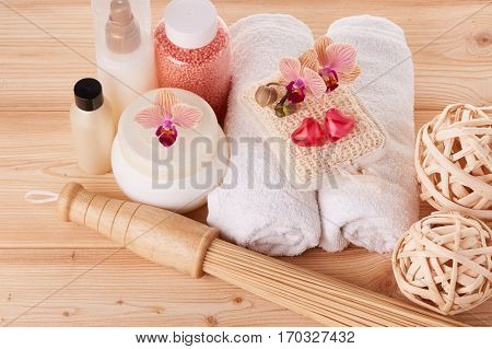 Spa still life on a wooden background. Healthy lifestyle, body care, bathhouse, Spa treatment and relaxation concept. Bamboo massage stick, towel, moisturizing cream and other toiletry.