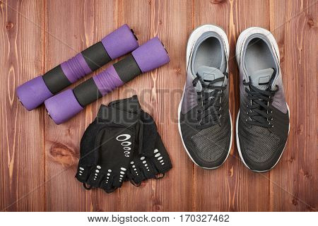 Dumbbells, sneakers and sport accessories on a wooden floor. Top view. Fitness, sport and healthy lifestyle concept.