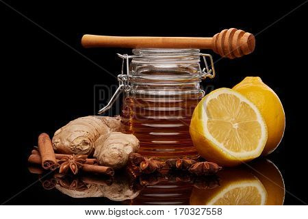Natural honey in a pot , honey dipper, lemon, ginger and spices on a black background.