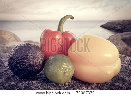 Two capsicums with lemon and avocado in seashore