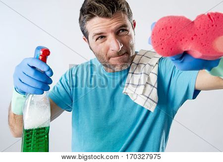 portrait of domestic service man or busy husband concentrated doing house cleaning with spray bottle and sponge washing glass carefully pointing the camera isolated even background